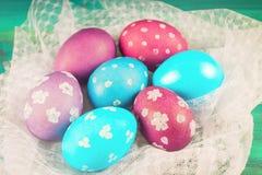 Фиолетовые и голубые пасхальные яйца на белой ткани деревянное предпосылки голубое пасха счастливая Стоковая Фотография RF