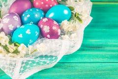 Фиолетовые и голубые пасхальные яйца на белой ткани деревянное предпосылки голубое пасха счастливая Стоковое Изображение RF