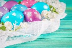 Фиолетовые и голубые пасхальные яйца на белой ткани деревянное предпосылки голубое пасха счастливая Стоковые Фотографии RF