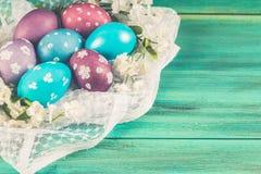 Фиолетовые и голубые пасхальные яйца на белой ткани деревянное предпосылки голубое пасха счастливая Стоковая Фотография