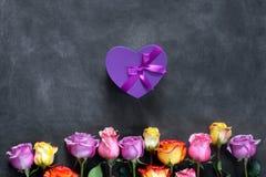 Фиолетовые и желтые розы, кладут настоящий момент в коробку на черной предпосылке Стоковое Изображение