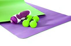 Фиолетовые и зеленые разминки циновки Зеленые гантели Стоковое Фото