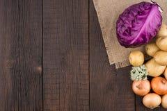 Фиолетовые капуста, картошки и луки на старой темной деревянной таблице Стоковые Изображения