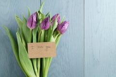 Фиолетовые тюльпаны на голубой деревянной предпосылке с я тебя люблю взгляд сверху карточки Стоковое Изображение