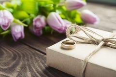 Фиолетовые тюльпаны с подарком и обручальным кольцом на деревянном столе Стоковые Фотографии RF