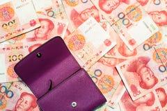 Фиолетовый бумажник помещенный на китайских банкнотах юаней Стоковое Изображение RF