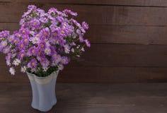 Фиолетовый резец цветет в вазе, на деревянной предпосылке Стоковое фото RF