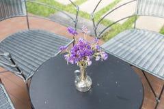 фиолетовый цветок в стеклянной вазе, плетеном стуле на патио Стоковое фото RF