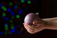 Фиолетовый шарик рождества в руках ребенк на черной предпосылке стоковая фотография rf
