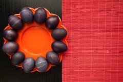 12 фиолетовых пасхальных яя на оранжевой плите, на черноте деревянной Стоковые Фотографии RF