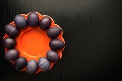 12 фиолетовых пасхальных яя на оранжевой плите, на черноте деревянной Стоковая Фотография RF
