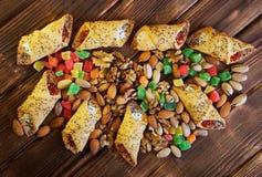Фисташки, candied плоды, миндалины, грецкие орехи и домодельные печенья с маковыми семененами и вареньем на деревенском деревянно стоковая фотография rf