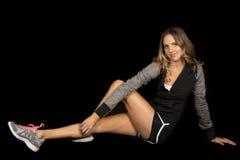 Фитнес женщины серый на черноте сидит ноги вне смотрит стоковое изображение