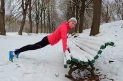 Фитнес и ход зимы в парке: счастливый бегун женщины нагревая и работая перед jogging в снеге Стоковые Изображения