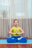 Фитнес концепция спорта, тренировки и образа жизни - ребенок делая тренировки на циновке в доме Стоковые Фотографии RF