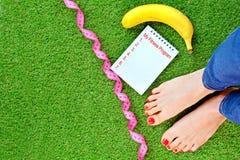 Фитнес-программа и концепция диеты с ногами женщины, лентой измерения, бананом и тетрадью на зеленой искусственной траве стоковые фото