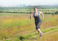Фитнес плюс бежать женщины размера внешний Стоковое фото RF