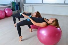 Фитнес, спорт, работая образ жизни - группу в составе женщины делая тренировки с гантелями и ballsin пригонки класс Pilates на Стоковое Изображение