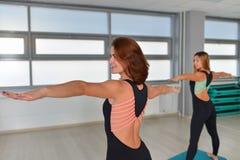 Фитнес, спорт, работая образ жизни - счастливую женскую одежду в bodysuits делая тренировки на спортзале стоковое фото rf