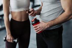Фитнес, спорт, технология и уменьшать - конец концепция вверх усмехаясь молодой женщины и личного тренера со смартфоном и водой стоковые фотографии rf
