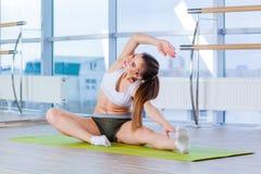 Фитнес, спорт, тренировка и концепция людей - счастливая молодая женщина протягивая перед бежать в спортзале стоковая фотография rf