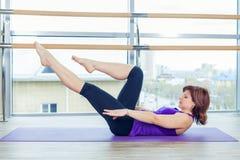 Фитнес, спорт, тренировка и концепция людей - усмехаясь женщина делая подбрюшные тренировки на циновке в спортзале стоковое изображение rf