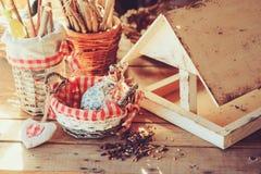 Фидер птицы с семенами на деревянном столе в уютном загородном доме, тонизированном годе сбора винограда Стоковое Изображение RF