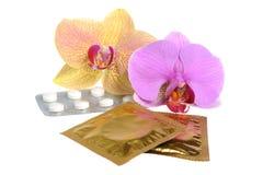 Фильм-покрытые таблетки и презервативы при 2 изолированного цветка орхидеи Стоковые Фото
