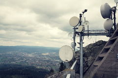 Фильтрованное изображение камеры слежения с передатчиками и антенны на радиосвязи возвышаются Стоковые Фотографии RF