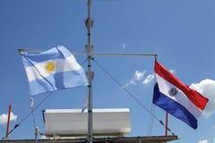 Флаги Аргентины и Парагвая с голубым небом на заднем плане стоковые фотографии rf