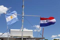 Флаги Аргентины и Парагвая с голубым небом на заднем плане стоковое фото