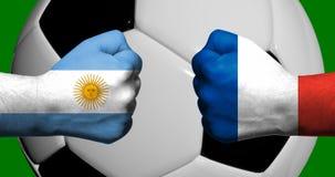 Флаги Аргентины и Франции покрашенных на 2 сжатых кулаках смотря на один другого с футбольным мячом крупного плана 3d на заднем п стоковое фото
