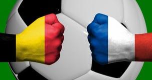 Флаги Бельгии и Франции покрашенных на смотреть на 2 сжатых кулаков Стоковое Изображение RF