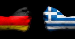 Флаги Германии и Греции покрашенных на смотреть на 2 сжатых кулаков Стоковые Фото