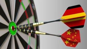 Флаги Германии и Китая на дротиках ударяя яблочко цели Международное сотрудничество или конкуренция схематические стоковое фото rf