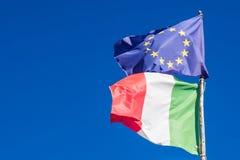 Флаги Италии и Европейского союза в небе предпосылки голубом стоковые изображения