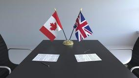 Флаги Канады и Великобритании и бумаги на таблице Переговоры и подписание международного соглашения акции видеоматериалы