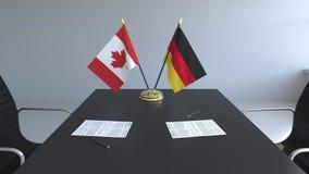 Флаги Канады и Германии и бумаги на таблице Переговоры и подписание международного соглашения Схематическое 3D иллюстрация штока