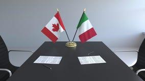 Флаги Канады и Италии и бумаги на таблице Переговоры и подписание международного соглашения Схематическое 3D иллюстрация штока