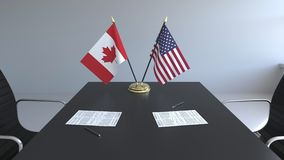 Флаги Канады и Соединенных Штатов и бумаги на таблице Переговоры и подписание международного соглашения акции видеоматериалы