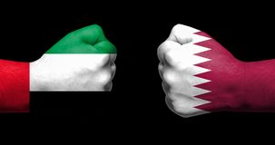 Флаги Катара и Саудовской Аравии покрашенных на 2 сжатых кулаках fa Стоковые Фотографии RF