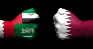 Флаги Катара и свои соседи покрашенные на 2 сжатых кулаках Стоковое Фото