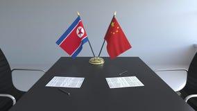 Флаги Корейской Северной Кореи и Китая и бумаги на таблице Переговоры и подписание международного соглашения схематическо иллюстрация вектора