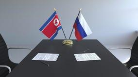 Флаги Корейской Северной Кореи и России и бумаги на таблице Переговоры и подписание международного соглашения схематическо акции видеоматериалы
