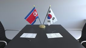 Флаги Корейской Северной Кореи и Южной Кореи и бумаги на таблице Переговоры и подписание международного соглашения иллюстрация штока