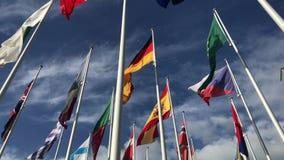 Флаги много стран развевая в ветре на голубом небе и белых облаках Политика, отношение, международная встреча, торговля,