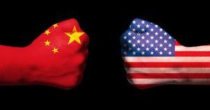 Флаги США и Китая на 2 сжатых кулаках смотря на один другого на черной концепции торговой войны фарфора предпосылки/США стоковое фото rf