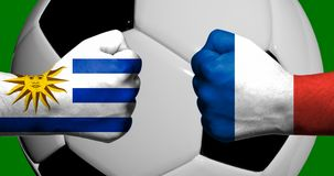 Флаги Уругвая и Франции покрашенных на смотреть на 2 сжатых кулаков Стоковое фото RF
