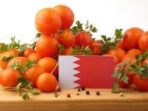 Флаг Бахрейна на деревянной панели при томаты изолированные на белизне Стоковое фото RF