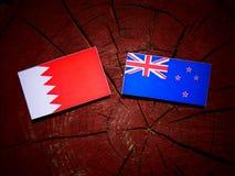 Флаг Бахрейна с флагом Новой Зеландии на изолированном пне дерева Стоковое Изображение